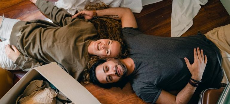 A couple on the floor smiling because they are successfully moving on a budget