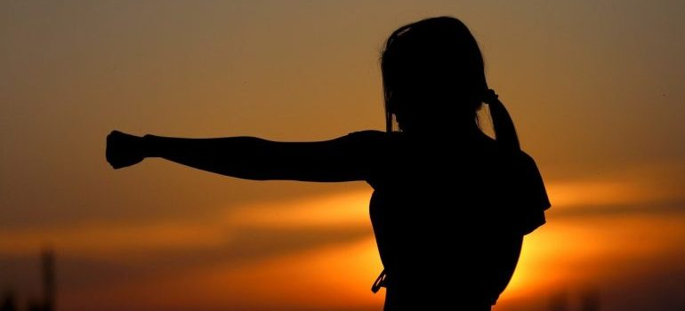 A silhouette of a woman in fighting stance.