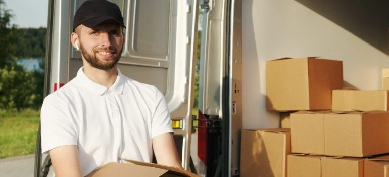 A mover, smiling, with boxes.