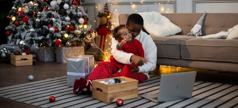 A parent and a child in a blanket, enjoying Christmas time.