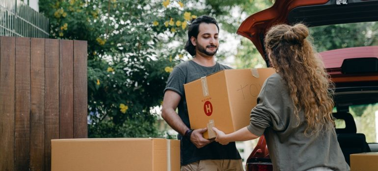 A man passing a moving box to a woman