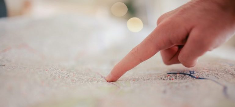A person pointing a finger at a certain location on a map.