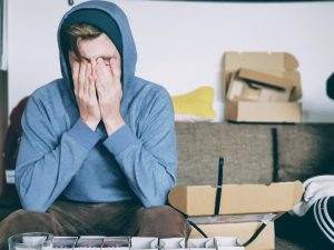 Man sitting next to boxes stressing because of things people forget about when moving