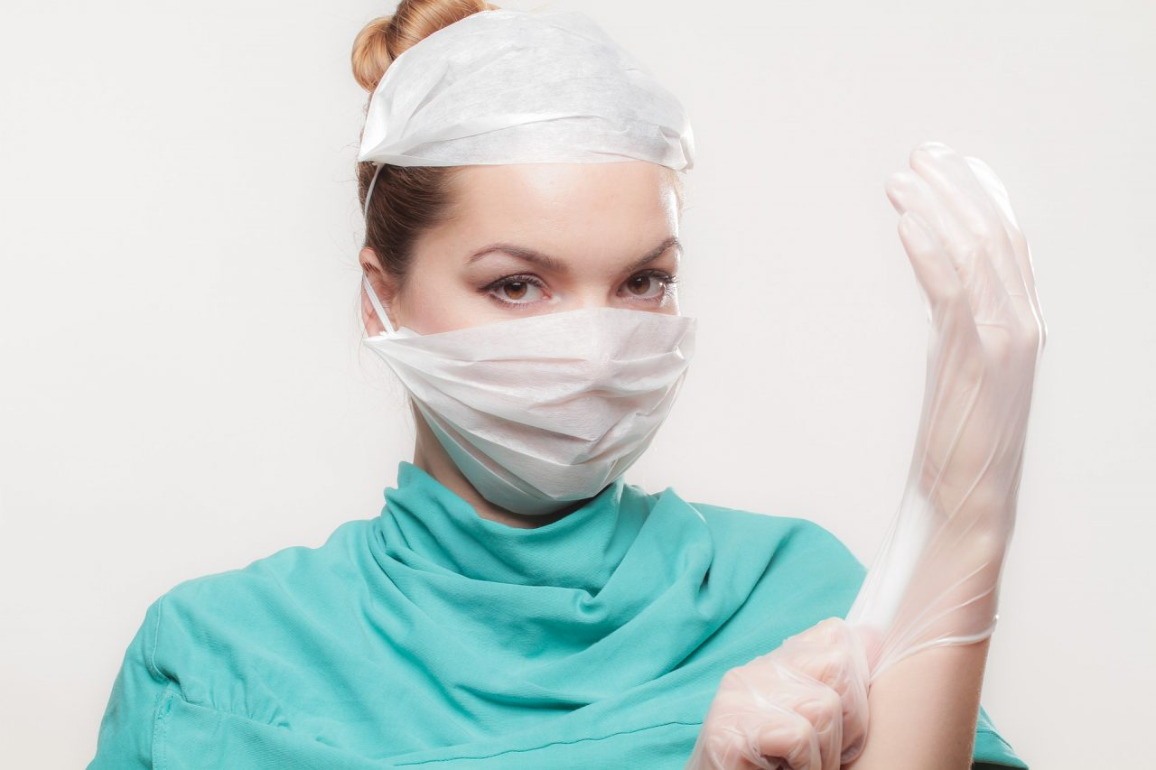 A nurse putting on a glove