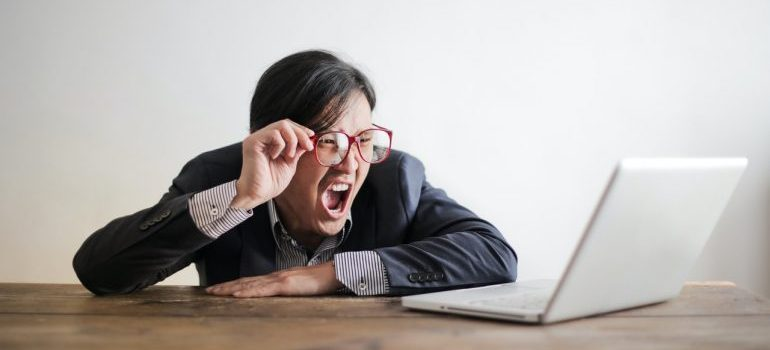 Frustrated man screaming at the laptop