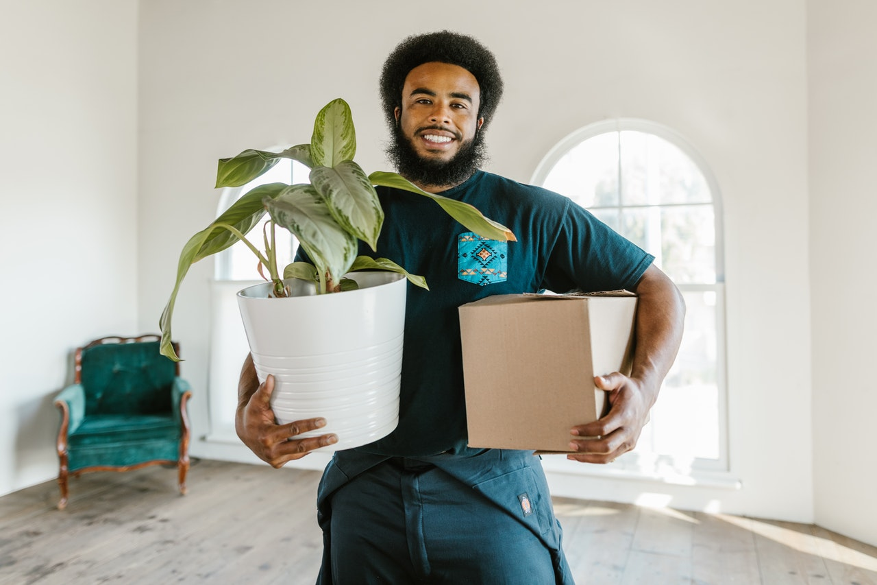 Man holding a box and a plant is why you should hire packing professionals