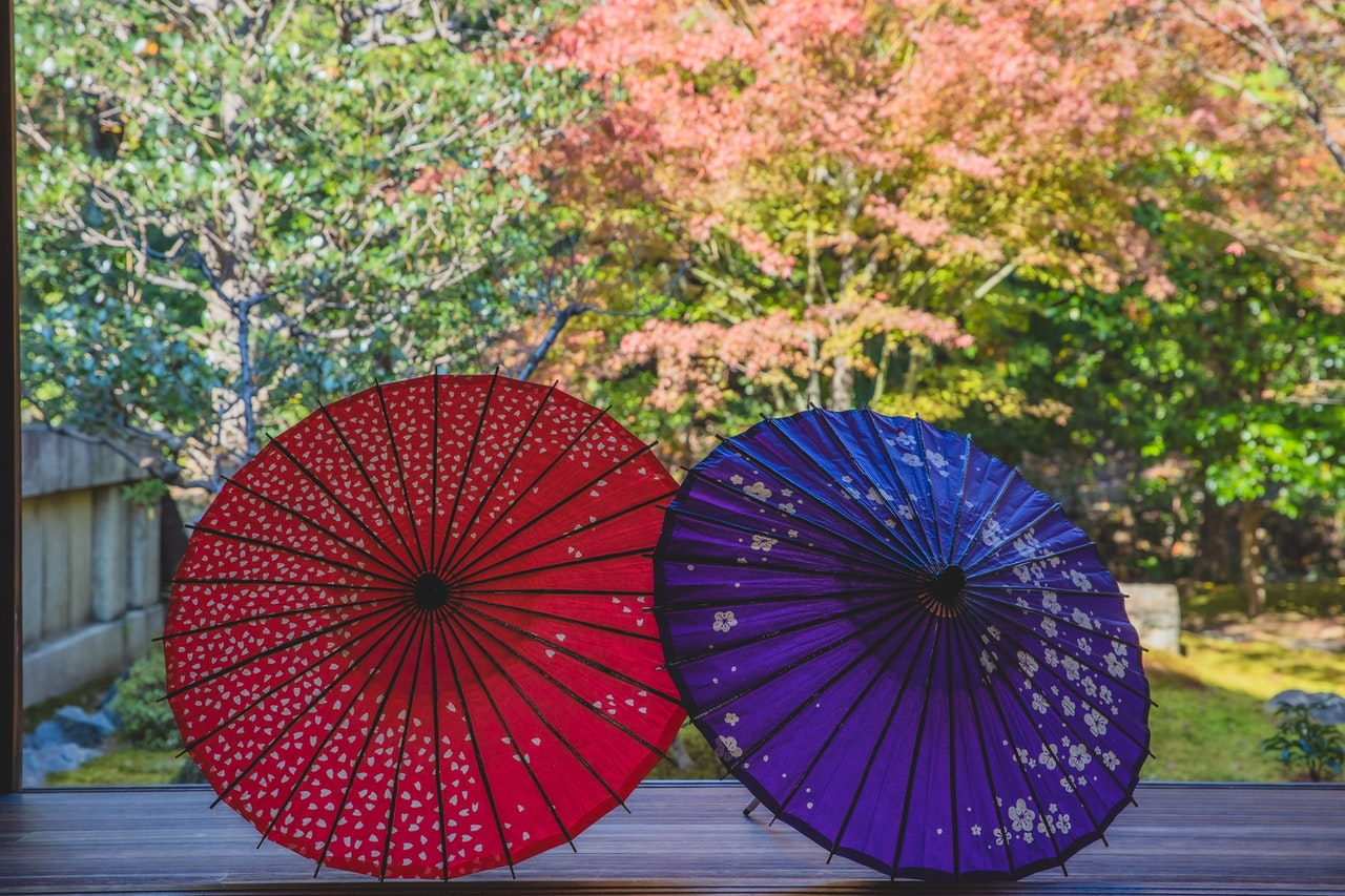 Red and blue umbrella with floral decorations in the small backyard