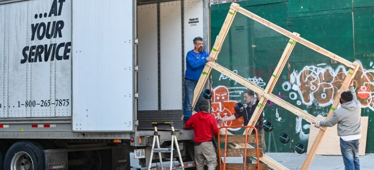 four people loading a moving truck