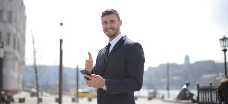 A businessman holiding smartphone and thumbs up for storage Maryland.