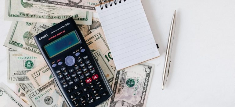 a calculator next to a notebook laying on a pile of money representing the ways you can manage costs of your long-distance move