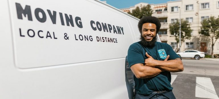 a mover standing next to a white moving company van