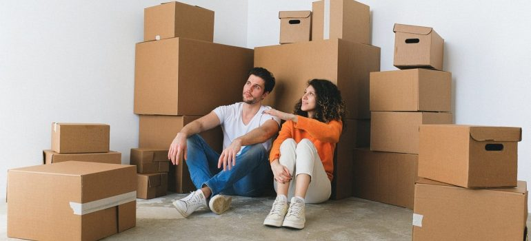 a couple sitting in-between a pile of cardboard boxes as they prepare to move to Rockville this fall
